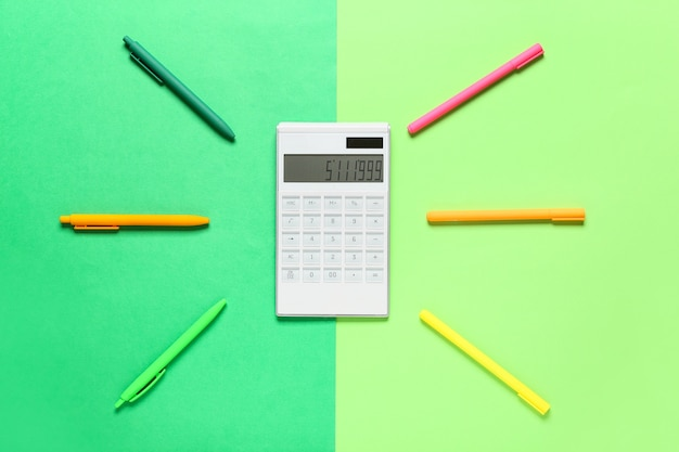 Calculadora moderna y papelería en superficie de color