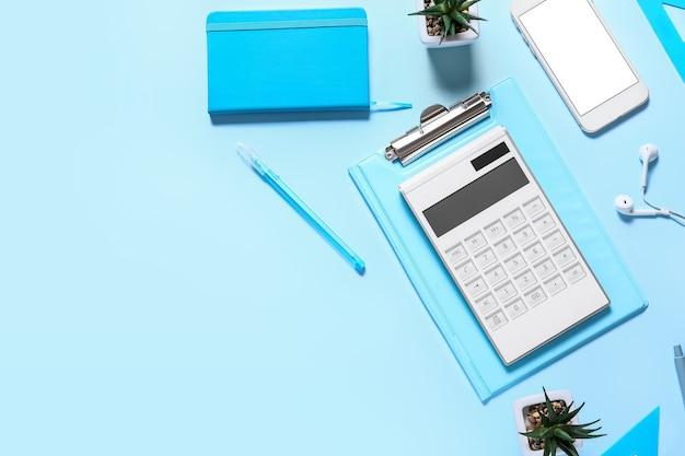 Calculadora moderna y papelería con teléfono móvil en superficie de color