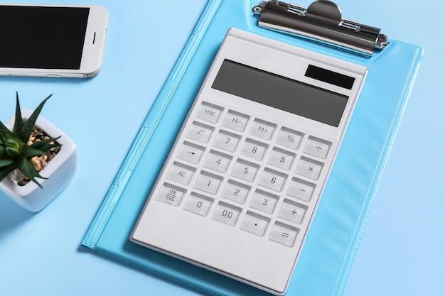 Calculadora moderna y portapapeles con teléfono móvil en superficie de color