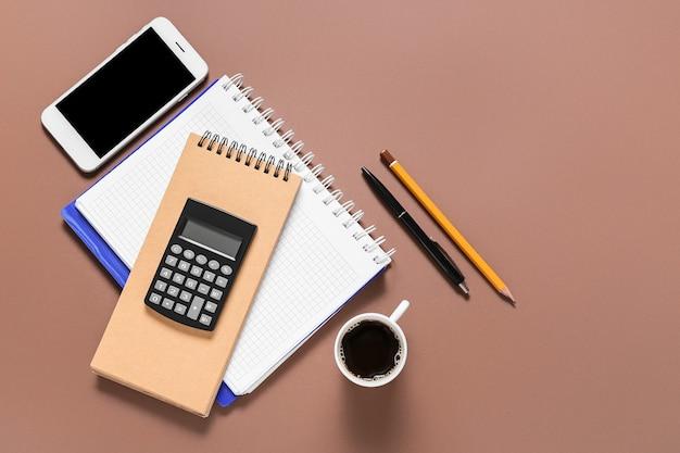 Calculadora moderna con teléfono móvil, taza de café y material de oficina en la superficie de color