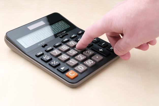 Una calculadora negra con botones grandes y una pantalla yace sobre una mesa beige, y un hombre presiona su dedo sobre la tecla número seis.