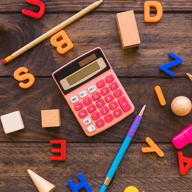 Calculadora y papelería en medio de letras y figuras geométricas
