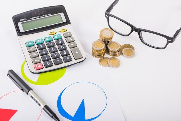 Calculadora con pilas de monedas en la mesa
