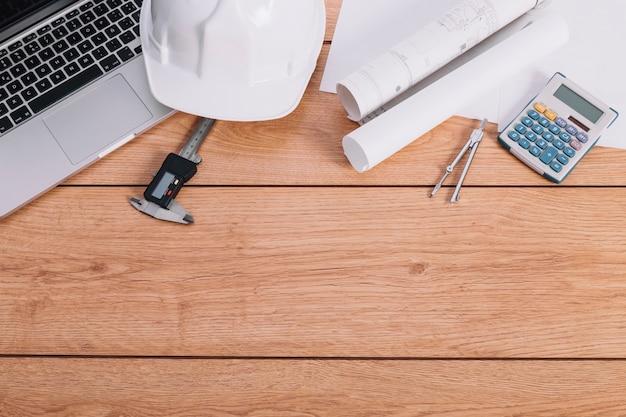 Calculadora y planos cerca del casco y la computadora portátil