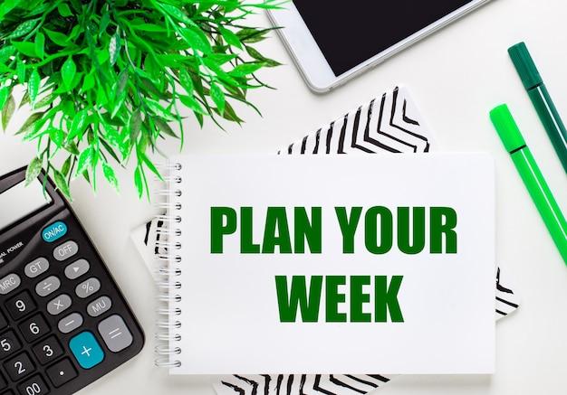 Calculadora, planta verde, teléfono, rotulador, cuaderno con el texto planifique su semana en el escritorio. endecha plana.