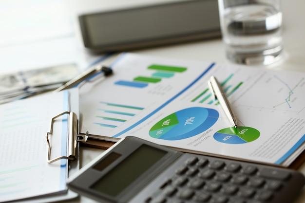 La calculadora plateada con teclado gris yace en el gráfico de escritorio y en la configuración de la oficina. cálculo de gastos familiares ingresos sociales población independiente concepto de investigación de crecimiento de situación de irs