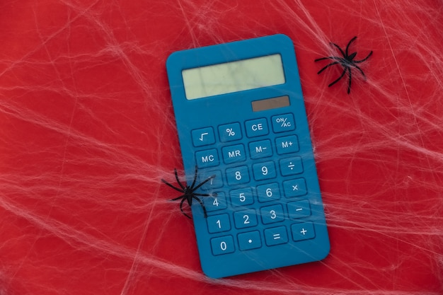 Calculadora en rojo con telarañas y arañas. tema de halloween. aracnofobia