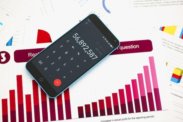 Calculadora de smartphone y estadísticas financieras en tableta de visualización en primer plano de mesa de oficina.