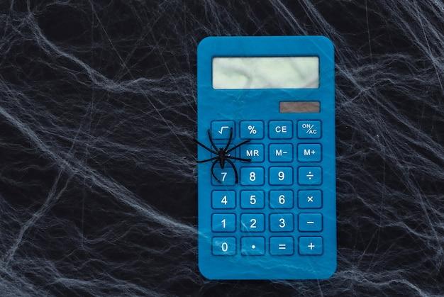 Calculadora sobre un fondo negro con telarañas y arañas. tema de halloween. aracnofobia