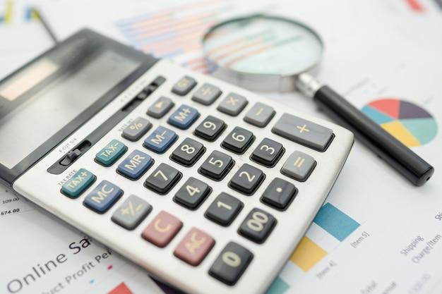 Calculadora sobre tabla y papel cuadriculado. desarrollo financiero, cuenta bancaria, estadísticas, economía de datos de investigación analítica de inversiones, comercio bursátil, concepto de empresa comercial.