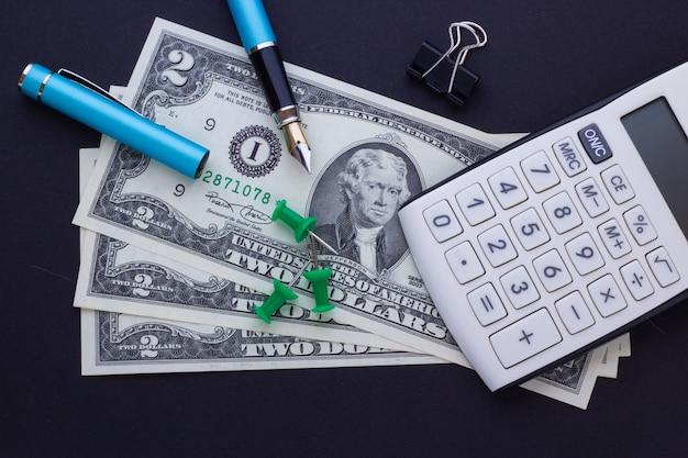 Calculadora, suministros de oficina y dólares en un fondo negro, concepto de negocio