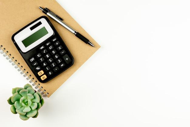 Calculadora y suministros de oficina en mesa blanca.