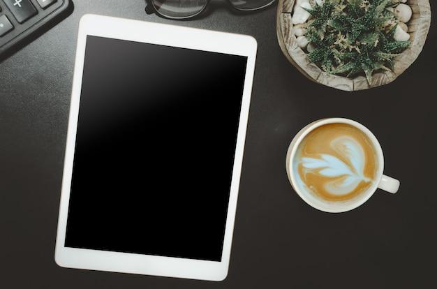 Calculadora de tableta topview y taza de café cactus en el escritorio