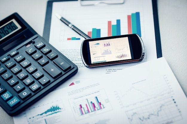Calculadora de telefonía móvil y gráficos financieros sobre la mesa