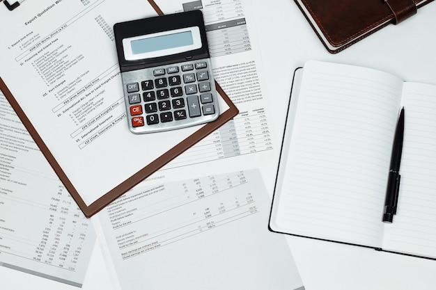 Calculadora en varios documentos y un cuaderno.
