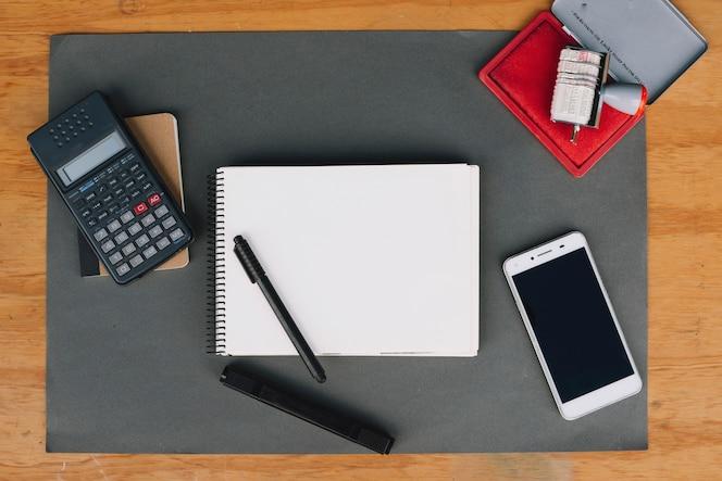 Calculadora y teléfono inteligente cerca de papelería