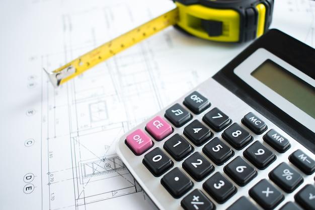 Calculadoras y cinta métrica colocadas sobre planos y herramientas de ingeniería.