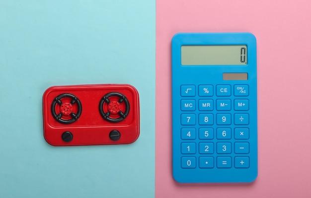 Cálculo de costes de gas o electricidad. calculadora y estufa de cocina de juguete sobre fondo pastel azul-rosa. vista superior