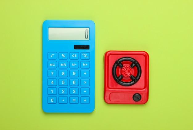 Cálculo de costes de gas o electricidad. estufa de cocina calculadora y juguete sobre fondo verde. vista superior