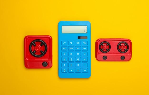 Cálculo de costes de gas o electricidad. estufas de cocina calculadora y de juguete sobre fondo amarillo. vista superior