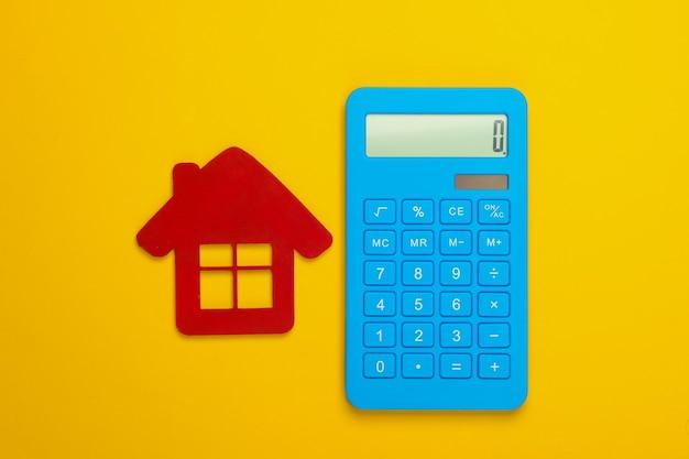 Cálculo del costo de la vivienda en alquiler. figurilla de la casa roja, calculadora sobre fondo amarillo. vista superior