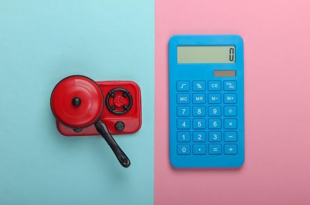 Cálculo de costos de gas. calculadora y estufa de cocina de juguete con sartén sobre fondo pastel azul-rosa. vista superior