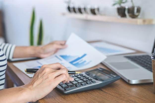 Cálculos contables femeninos, auditoría y análisis de datos de gráficos financieros con calculadora y computadora portátil