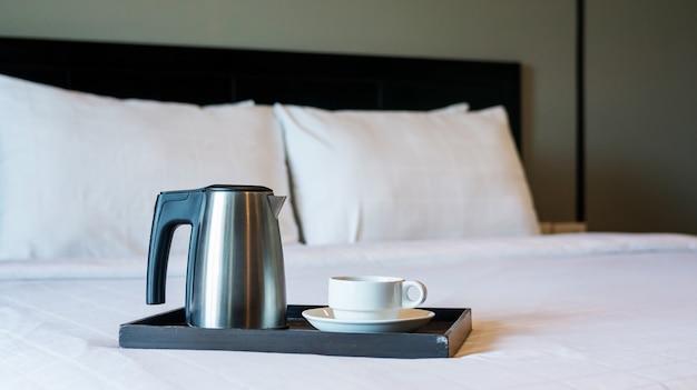 Caldera y una taza blanca en la cama preparan para un desayuno.