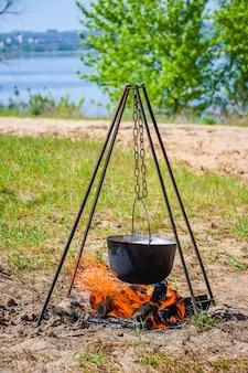 En el caldero negro en el fuego preparar gachas.