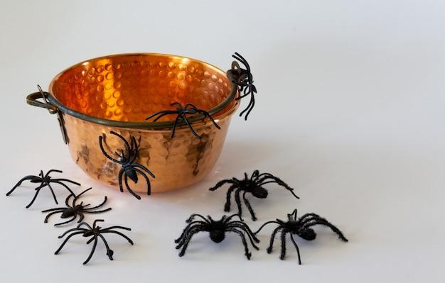 Caldero viejo con arañas de juguete. fondo de halloween. enfoque selectivo. copie el espacio.