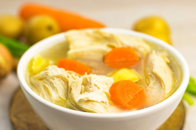 Caldo de estofado de sopa de pollo y verduras en un tazón blanco sobre la vieja tabla de cortar de madera rústica. de cerca. enfoque selectivo. copia espacio