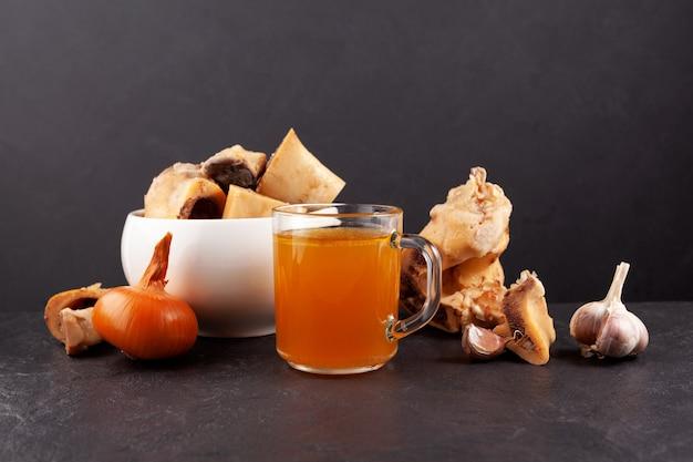 Caldo de hueso de res en taza transparente sobre fondo oscuro los huesos contienen colágeno