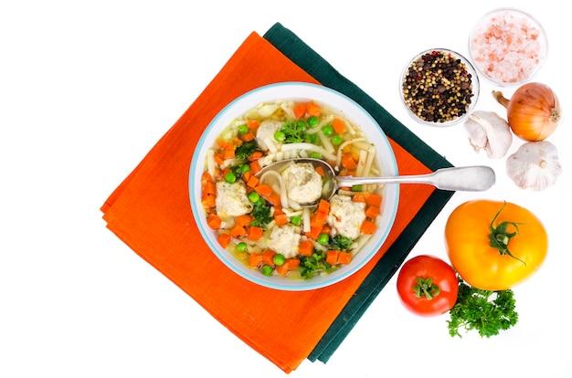 Caldo de pollo con verduras, pastas y albóndigas.