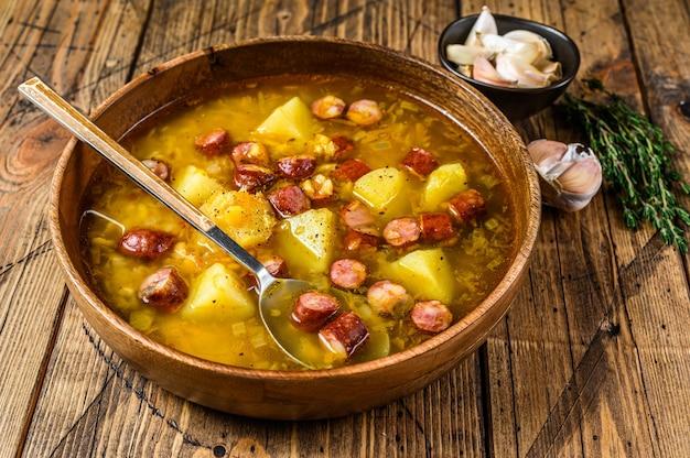 Caldo sopa de guisantes con salchichas ahumadas en una placa de madera