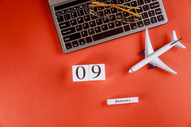 Calendario del 09 de enero con accesorios en el espacio de trabajo comercial escritorio de oficina en el teclado de la computadora, avión, gafas fondo rojo