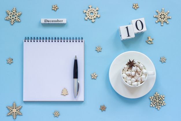 Calendario 10 de diciembre taza de cacao y malvavisco, libreta abierta vacía