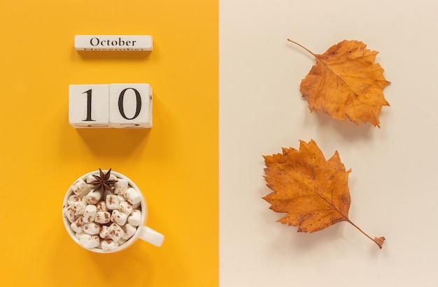 Calendario 10 de octubre, taza de cacao con malvaviscos y hojas amarillas de otoño
