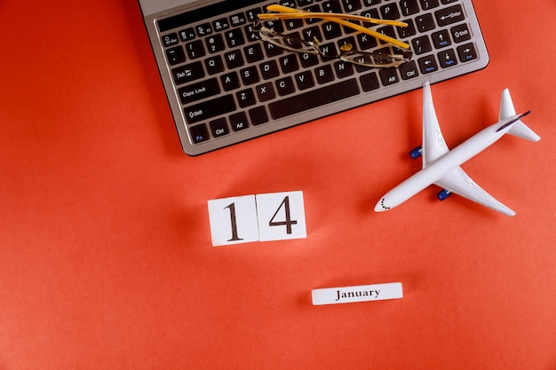 Calendario del 14 de enero con accesorios en el espacio de trabajo comercial escritorio de oficina en el teclado de la computadora, avión, gafas fondo rojo