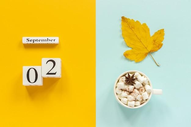 Calendario 2 de septiembre, taza de cacao con malvaviscos y hoja amarilla de otoño