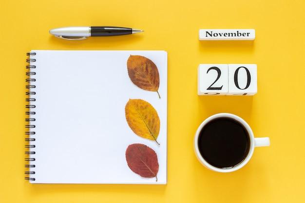 Calendario 20 de noviembre taza de café, bloc de notas con bolígrafo y hoja amarilla sobre amarillo