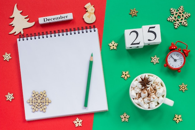 Calendario 25 de diciembre taza de cacao y malvavisco, libreta abierta vacía