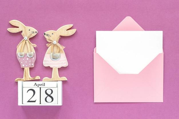 Calendario 28 de abril, par de conejitos de pascua de madera, sobre rosa.