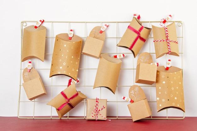 Calendario de adviento con cajas de cartón artesanales en el tablero de malla