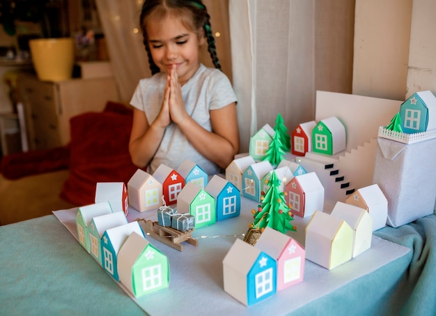 Calendario de adviento de origami. linda chica mirando pequeñas casas de papel con número