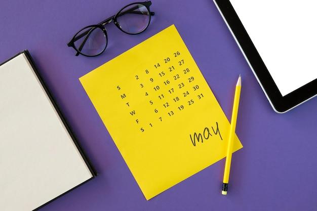 Calendario amarillo plano laico y gafas de lectura