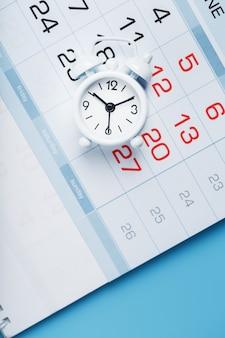 Calendario anual con un despertador blanco sobre fondo azul. el concepto de paso del tiempo y fechas significativas.