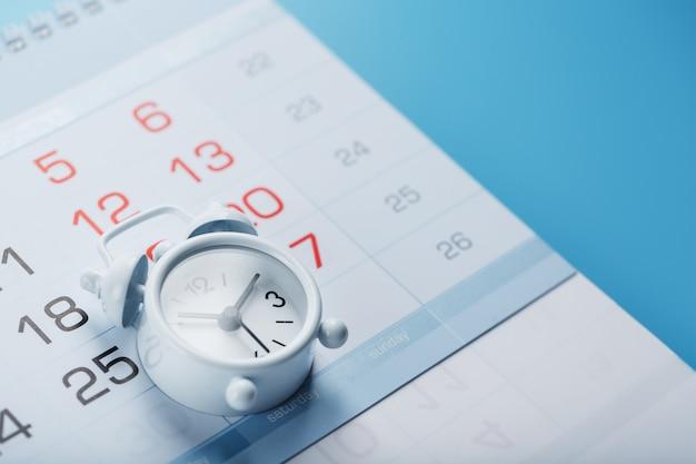 Calendario anual con un despertador blanco sobre un fondo azul.