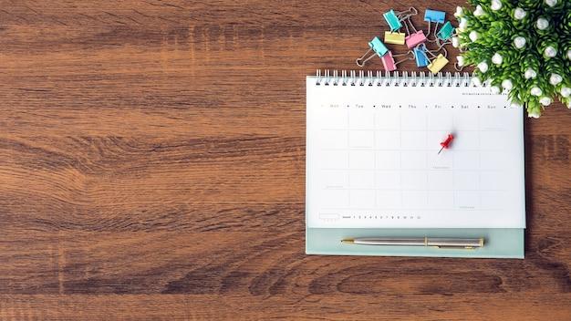 El calendario en blanco de la vista superior con un bolígrafo en el escritorio