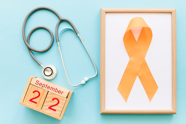 Calendario de bloque de madera 22 de septiembre, estetoscopio y cinta naranja para la conciencia múltiple