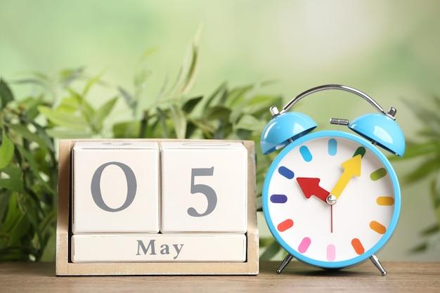 Calendario de bloque de madera y reloj despertador en la mesa contra el fondo verde borroso